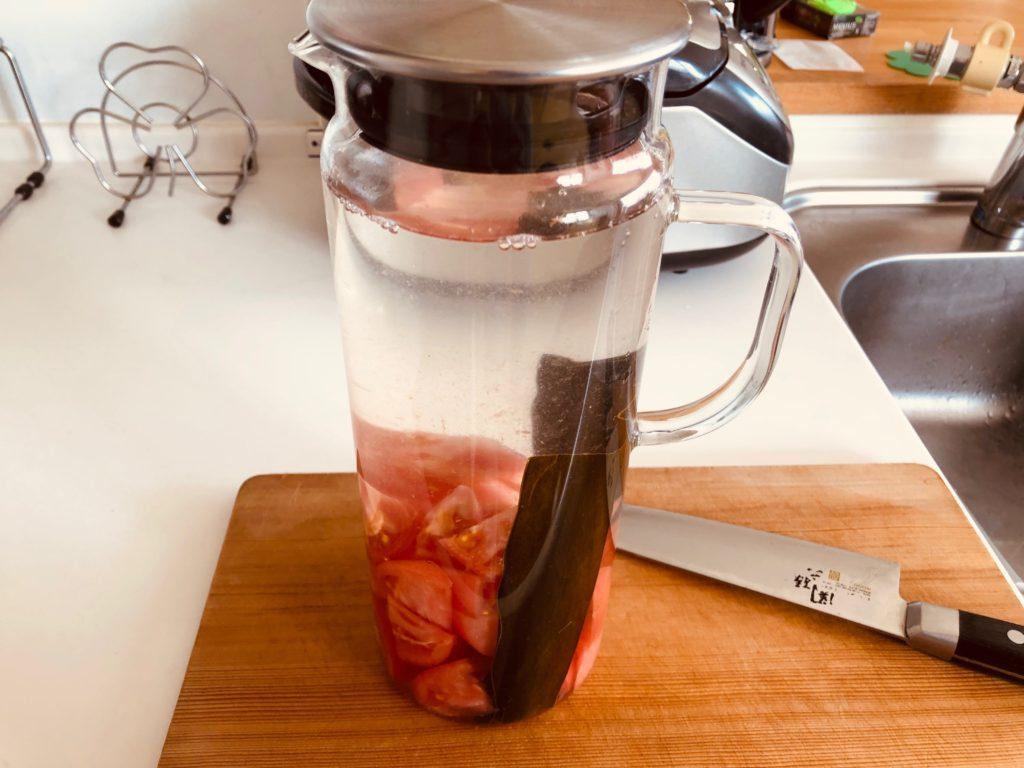 昆布とトマトが入った容器に水を入れる